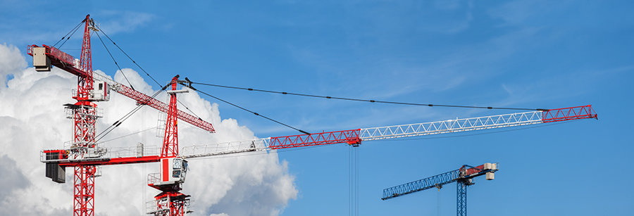 Lots of tower cranes on the blue sky background
